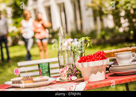Garden party food table, group of friends in background - Stock Photo