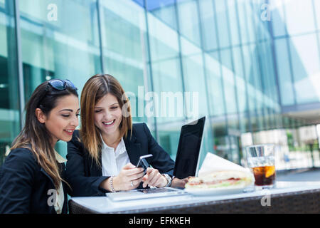 Businesswomen using laptop on working lunch - Stock Photo