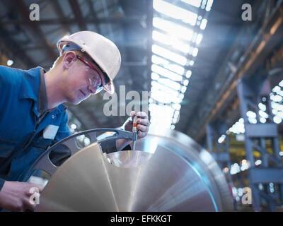 Engineer measuring steel part in engineering factory - Stock Photo