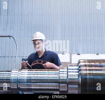 Apprentice working on lathe in engineering factory - Stock Photo