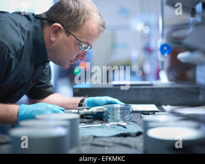Portrait of engineer measuring engineered part in factory - Stock Photo