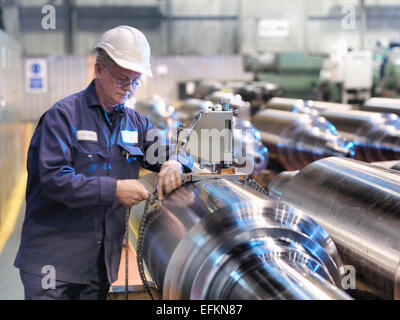 Hardness testing of steel part in engineering factory - Stock Photo