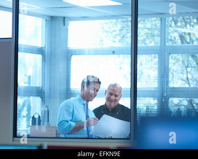 Engineer designers discussing plans in office - Stock Photo