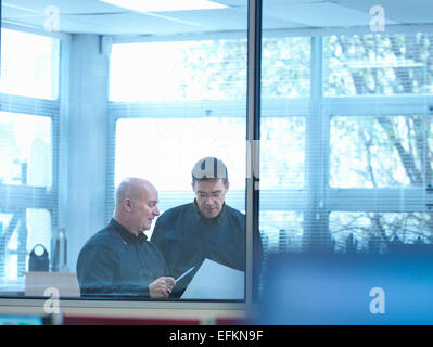 Two male engineer designers discussing plans in office - Stock Photo