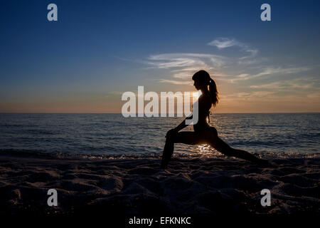 Silhouetted young woman practicing yoga at sunset, Oristano, Sardinia, Italy - Stock Photo
