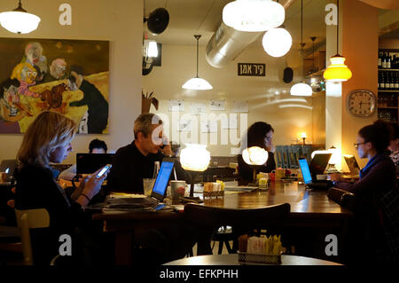 People using computers and cellular phones in a Nechama Vahetzi coffee shop in central Tel Aviv Israel - Stock Photo