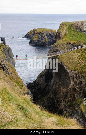 People crossing the Carrick-a-rede rope bridge on the North Antrim coast, Northern Ireland. - Stock Photo