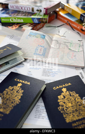 Preparation for International vacation travel with guide books, airfare itinerary, and Canadian passports - Stock Photo