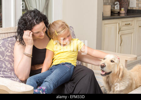 Mother and daughter sitting together on a chair on the porch of their home while stoking the golden retriever pet - Stock Photo