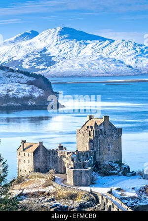EILEAN DONAN CASTLE IN WNTER WITH A BLUE LOCH DUICH AND HEAVY SNOW ON THE MOUNTAINS - Stock Photo