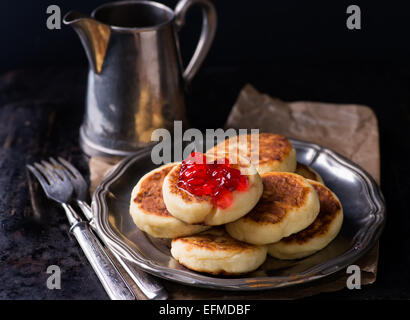 Cottage cheese pancakes with currant jam on vintage metal plate, selective focus - Stock Photo