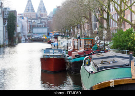 Houseboats on the Spielgelgracht canal with a view towards the Rijksmuseum in Amsterdam - Stock Photo