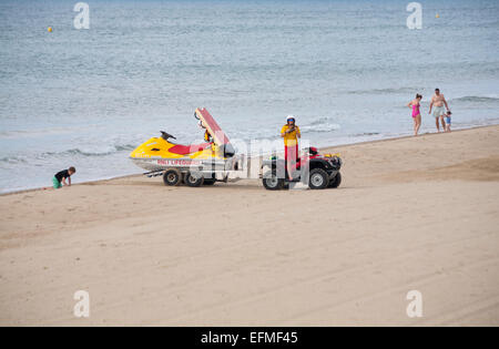 RNLI Lifeguard drives buggy towing jetski to the sea at Bournemouth in June - Stock Photo