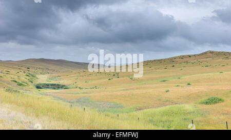 Open prairie grassland, and dry scrub and hills under a threating  sky near Vermilion, Nebraska, USA. - Stock Photo