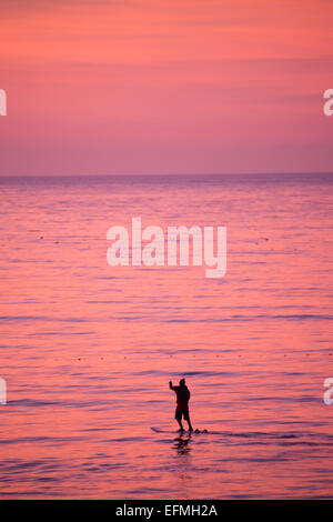 Aberystwyth, Wales, UK. 7th February, 2015. UK weather: A young man paddle-boarding on the flat calm sea at sunset - Stock Photo