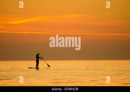 Aberystwyth, Wales, UK. 7th February, 2015. UK weather: A young woman stand-up paddle-boarding on the flat calm - Stock Photo