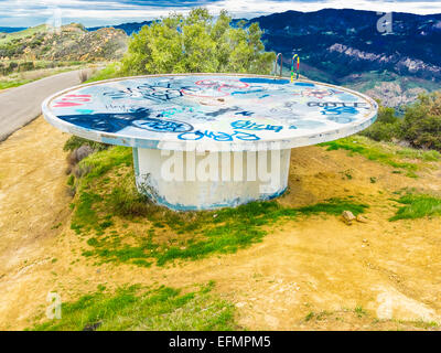 An abandoned concrete structure that resembles a flying saucer covered with paint splotches where graffiti once - Stock Photo