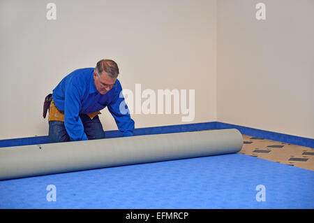A floorlayer rolls out the new carpet in a floorlaying job - Stock Photo
