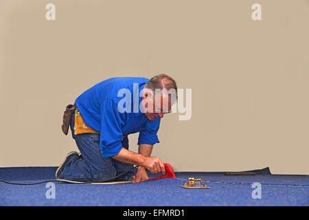A floorlayer uses a hot iron to seal the glue strip in a join a new carpet - Stock Photo