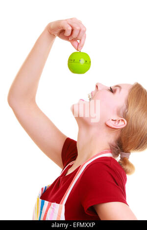 Funny housewife or chef in colorful kitchen trying to eat apple timer eggtimer making fun isolated studio shot - Stock Photo