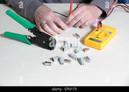 hands using a digital multimeter tester to test a RJ45 connector - Stock Photo