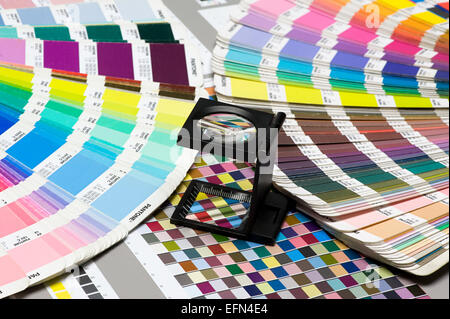 Close up Small Magnifying Glass Device on Top of Pantone Color Guide Above the Table. - Stock Photo