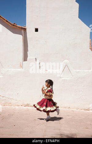 Little girl dressed up for Sept 18 Independence Day holiday dances in front of adobe San Pedro church, San Pedro, - Stock Photo