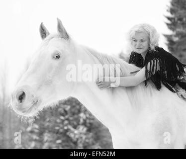 Attractive blond woman hugs a white horse, overcast winter day - Stock Photo