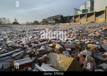 piles of rubble on derelict land and factory building covered by winter snow near selby yorkshire united kingdom - Stock Photo