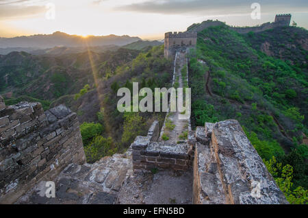 The 2,300 year old Great Wall of China is illuminated by the setting sun. - Stock Photo