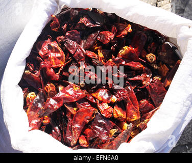 A white bag full of dry red papers - Stock Photo