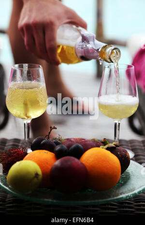 A man's hand pours champagne into two glasses. A plate of exotic fruits is in the front. - Stock Photo