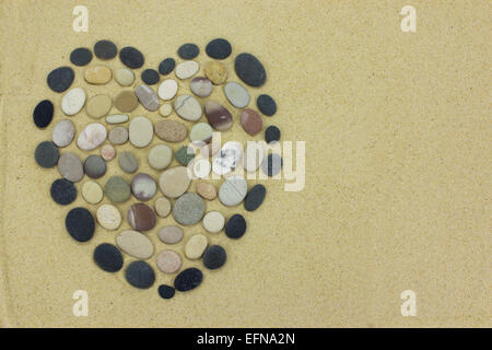 Heart shape made from beach stones or pebbles on golden sand. - Stock Photo