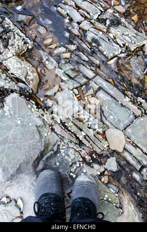Hiker in winter boots standing on rocky shoreline. - Stock Photo