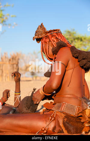 A Himba woman making traditional braids on a young girl, Namibia. - Stock Photo