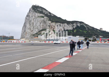 Gibraltar rock Cars and pedestrians cross the runway of Gibraltar airport at the border of Spain and Gibraltar. - Stock Photo
