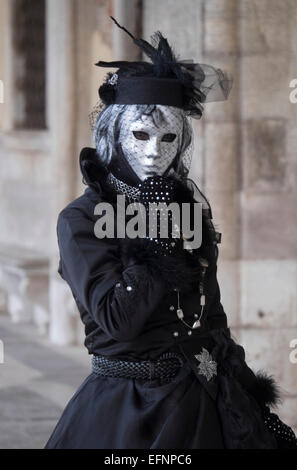 A reveller wearing elaborate costume and mask poses for th camera during the Carnival of Venice, Italy - Stock Photo
