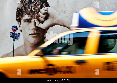 Handsome young male model on fashion advertising billboards at bus stop, yellow cab taxi motion blur passing. 5th - Stock Photo