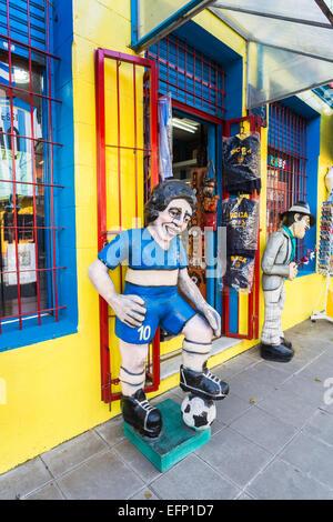 Effigy of local football player hero Diego Maradona in the colours of Boca Juniors outside a sport souvenir shop - Stock Photo