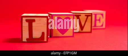 Valentine's day decoration with the word love in wooden alphabet blocks on a red background - Stock Photo