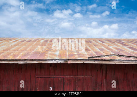 Building with rusty tin roof with clouds overhead. - Stock Photo
