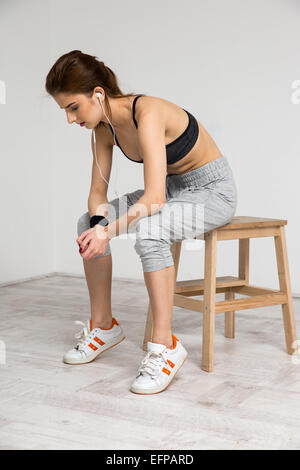 Portrait of a beautiful sports woman sitting on the wooden chair at gym - Stock Photo