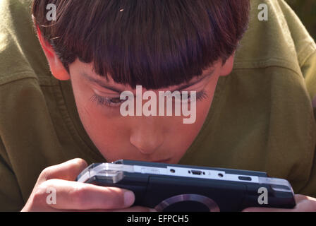 Intensive concentration and engagement with portable games console playing games outside looking at screen - Stock Photo
