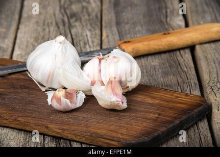 Garlic on old wooden breadboard - Stock Photo