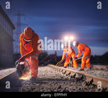 Railway maintenance workers using grinder on track at night - Stock Photo