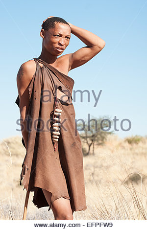Bushman wearing an animal skin leather tunic stands with hand on head looks across plains on a hunt in the Kalahari, - Stock Photo