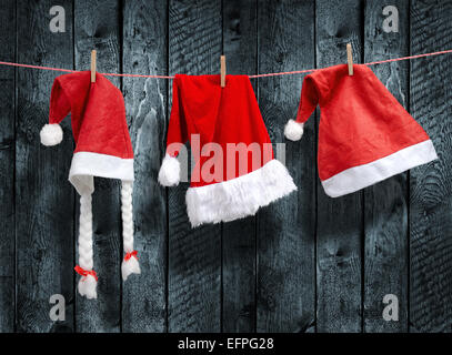 Three Santa Claus hat hanging on a clothesline - Stock Photo