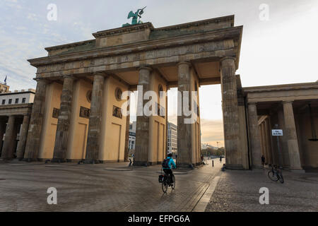 Cyclist approaches the Brandenburg Gate in the early morning, Historic Mitte, Berlin, Germany, Europe - Stock Photo