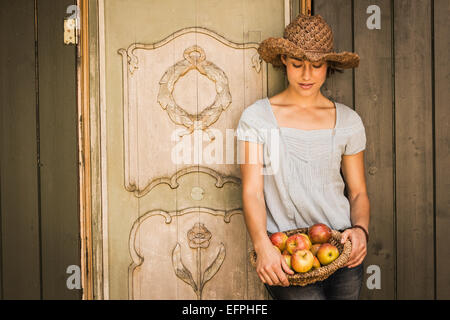Young woman wearing straw hat, leaning against shed, holding basket of apples - Stock Photo