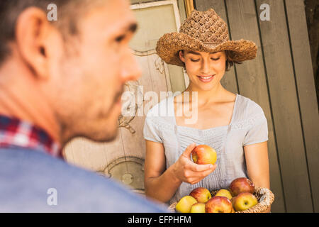 Young woman wearing straw hat, holding apple from basket, mid adult man in foregound - Stock Photo